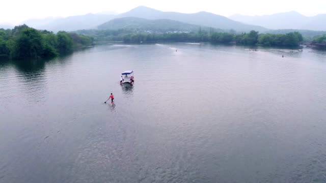 Chinese kayaking athlete practicing on lake, real time.
