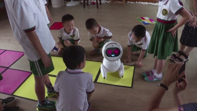 chinese kindergarten students giggle as they work to solve puzzles assigned by their new teaching assistant: a roundish short educator with a screen... - preschool stock videos & royalty-free footage