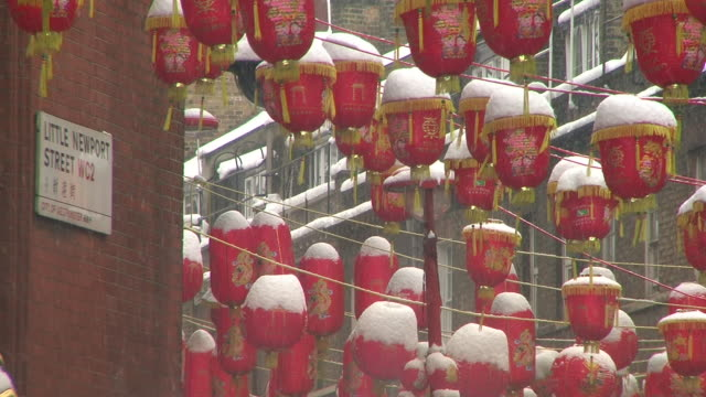 cu chinese lanterns covered in snow hanging above little newport street, chinatown, london, united kingdom - chinatown stock videos & royalty-free footage