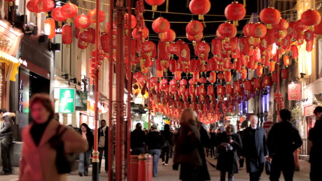 ms, selective focus, chinese lanterns hanging above gerrard street, chinatown, london, england - chinatown stock videos & royalty-free footage