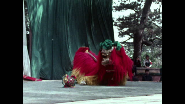 chinese lion plays with a ball on stage; china, 1973 - animal representation stock videos & royalty-free footage