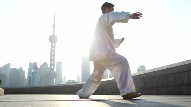 ws la chinese man doing tai chi on shanghai bund in morning - カンフー点の映像素材/bロール