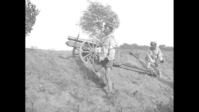 chinese men at the top of a breastwork with a small cannon a soldier scrambles up the incline to shove a ramrod down the gun's barrel and it fires /... - 1927 bildbanksvideor och videomaterial från bakom kulisserna