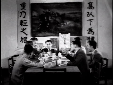 1944 Chinese men in Western business suits sitting at table in restaurant / China