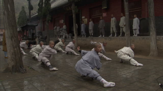 chinese monks perform martial arts in unison. - monk stock videos & royalty-free footage