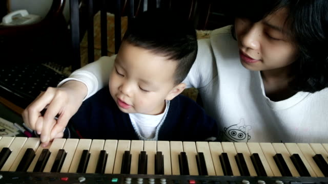Chinese mother and son having fun with keyboard with sound