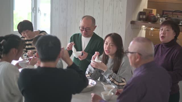 vídeos de stock, filmes e b-roll de família chinesa multi geração desfrutando glutinoso bola de arroz tang yuan sobremesa durante o solstício de inverno festival de ano novo chinês - família de várias gerações