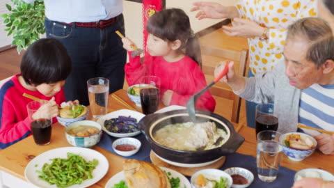 vídeos y material grabado en eventos de stock de familia china de múltiples generaciones comiendo años nuevos comida - mesa de comedor