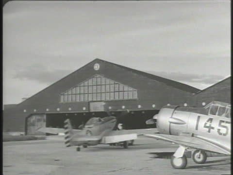 vídeos de stock e filmes b-roll de chinese nationalist pulling jet fighter airplane into hangar various engineers rebuilding damaged aircrafts lowering damaged fuselage taiwan formosa... - baixar