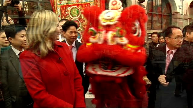 chinese new year celebrations; england: london: chinatown: ext reporter to camera chinese people along in street and browsing market stalls bunting... - chinesisches laternenfest stock-videos und b-roll-filmmaterial