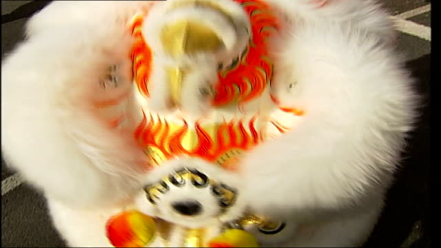chinese new year celebrations in london/'china in london' launched england london ext performers dancing in street with chinese dragon as celebrating... - headdress stock videos & royalty-free footage