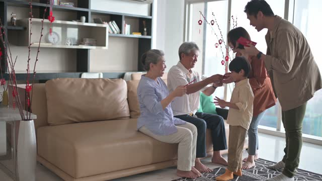 chinese new year family reunion couple with their child visiting grandparent home giving angpao red envelope red packet to parents prosperity happiness - traditional ceremony stock videos & royalty-free footage