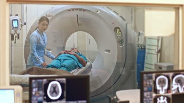 vídeos de stock, filmes e b-roll de enfermeira chinesa que ajuda o paciente durante o exame da varredura do gato - tomografia