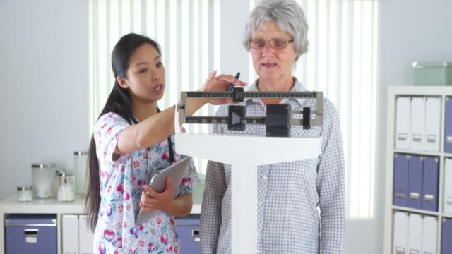 chinese nurse weighing elderly patient - mass unit of measurement stock videos and b-roll footage