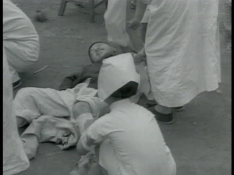 chinese nurses wrapping bandages on boy ws refugees receiving money crowd bg ms elderly lady bowing ms boy scouts pushing large wooden tank... - 1937 stock videos and b-roll footage