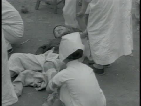 chinese nurses wrapping bandages on boy ws refugees receiving money crowd bg ms elderly lady bowing ms boy scouts pushing large wooden tank... - pojkscout bildbanksvideor och videomaterial från bakom kulisserna