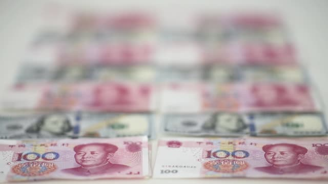 chinese one hundred yuan banknotes and u.s. one hundred dollar bills are arranged and counted in hong kong, china, on monday, july 20, 2015 - exchange rate stock videos & royalty-free footage