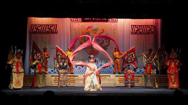 ms chinese opera actress performing traditional drama on stage in theater / xi'an, shaanxi, china - 腰に手を当てる点の映像素材/bロール