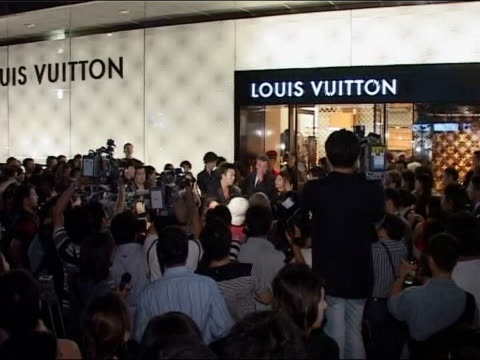 stockvideo's en b-roll-footage met int chinese people at ferrari stall hand holding bank notes people buying ferrari merchandise ext gv tent with sign 'official team merchandise'... - louis vuitton modelabel