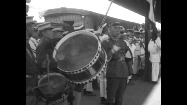 chinese people in traditional dress stand as a locomotive and passenger cars slow in a train station / drummers with a man 'conducting' with sword /... - manchuria stock videos & royalty-free footage