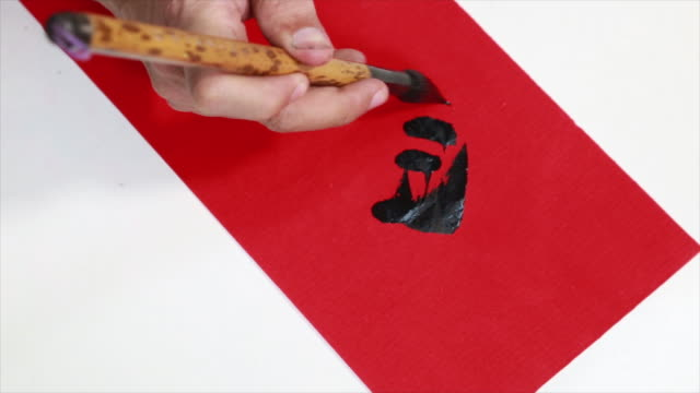 Chinese people writing Chinese Calligraphy