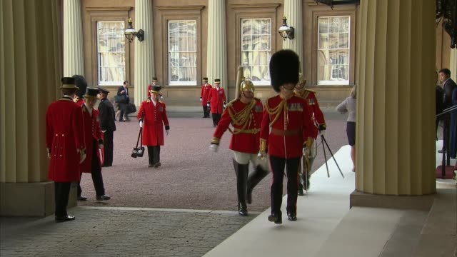 carriage arrival at buckingham palace dignatories military officers in ceremonial uniforms and members of the royal household preparing for the... - buckingham palace stock-videos und b-roll-filmmaterial