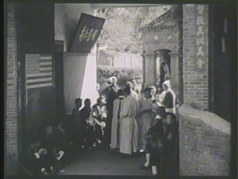 chinese refugees gathered in outdoor hall, us missionaries helping. american male doctor checking over chinese baby. vs chinese families sitting,... - missionary stock videos & royalty-free footage