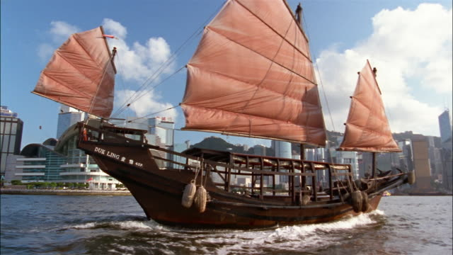 vidéos et rushes de a chinese sailing vessel sails in a harbor in front of the hong kong skyline. - jonque
