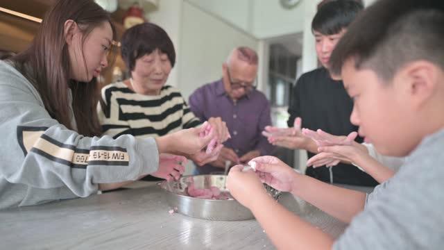中国の高齢者家族は、中国の新年の再会ディナーのために中華料理「唐元」のもち米球を準備します - ダンプリング点の映像素材/bロール