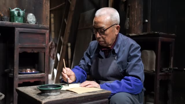 Chinesischer Senioren-Mann, der chinesische Kalligraphie schreibt