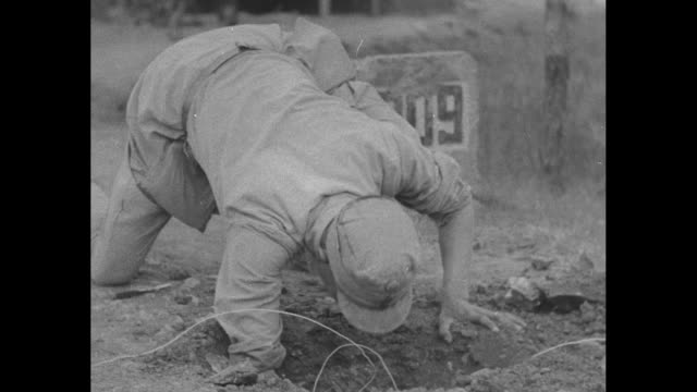 vídeos de stock, filmes e b-roll de vs chinese soldiers digging on burma road with pickaxes man packs bundle of dynamite and places it in hole and another turns the detonation box / two... - detonador