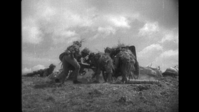 Chinese soldiers fire machine guns while the infantry crawls forward to attack the enemy during World War II