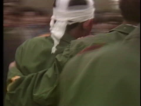 chinese soldiers help an injured and bloodied comrade away from the student demonstration in tiananmen square. - tiananmen square点の映像素材/bロール