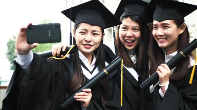 chinesische studenten, die selfies während der abschlussfeier machen. - east asian ethnicity stock-videos und b-roll-filmmaterial
