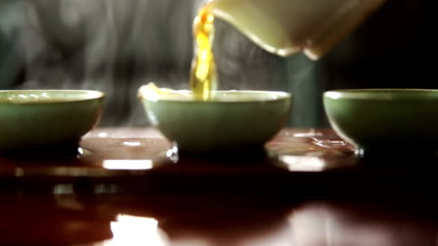 chinese tea is poured into three porcelain cups. - chinese tea cup stock videos and b-roll footage