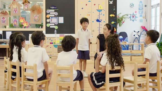 vidéos et rushes de chinese teacher teaching a class in classroom,4k - enseigner