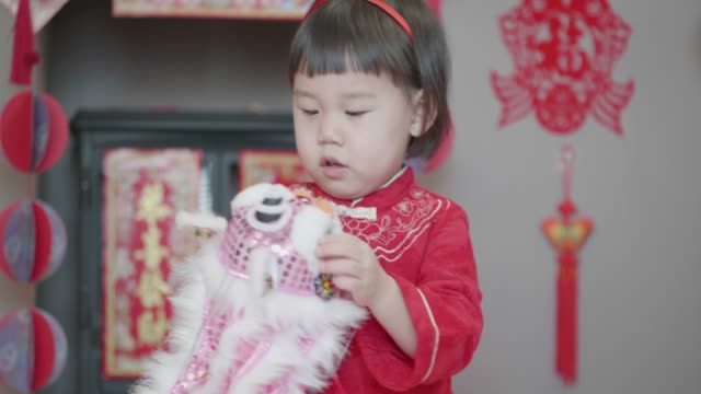 chinese toddler girl celebrating chinese new year at home - chinese new year stock videos & royalty-free footage