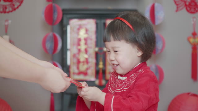chinese toddler girl celebrating chinese new year get red envelop  at home - chinese new year stock videos & royalty-free footage