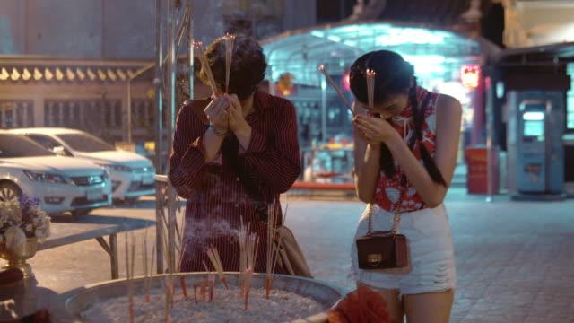 Chinese tourist praying at temple in Bangkok, Thailand.