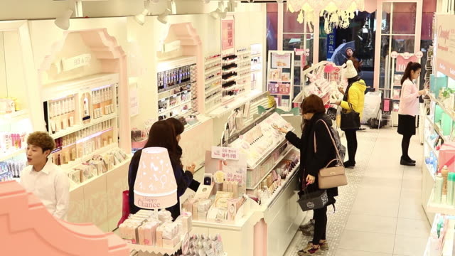 stockvideo's en b-roll-footage met chinese tourists browse cosmetics at amorepacific corp etude house store in the myeongdong shopping district in seoul south korea on monday feb 16... - korea