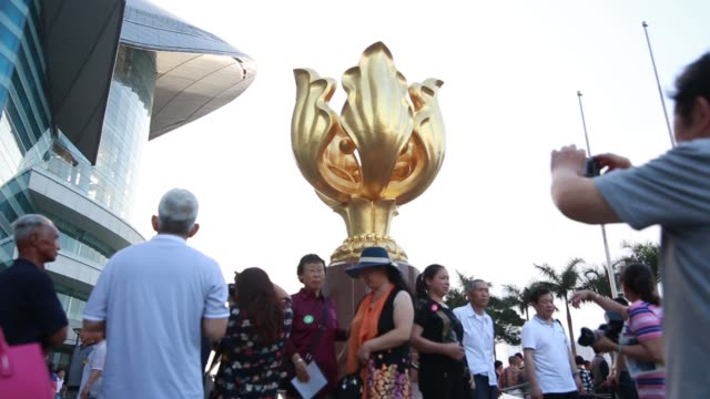 ms chinese tourists pose for photographs in front of a sculpture of a gilded bauhinia at golden bauhinia square at dusk ws touts selling photographs... - gilded stock videos & royalty-free footage