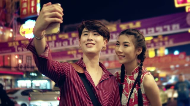 chinesische reisende paar unter selfies in der stadt. - chinesische kultur stock-videos und b-roll-filmmaterial