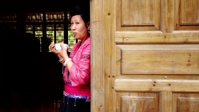 Chinese woman eating rice in traditional clothes
