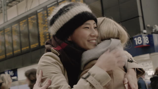 chinese woman greets and embraces female friend at railroad station - two people stock videos & royalty-free footage