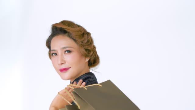 vídeos de stock e filmes b-roll de ms chinese woman in cheongsam holding shopping bag against white background - só mulheres de idade mediana