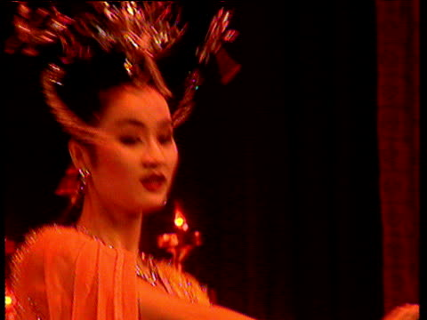Chinese woman in orange and ornate head dress performs traditional dance China