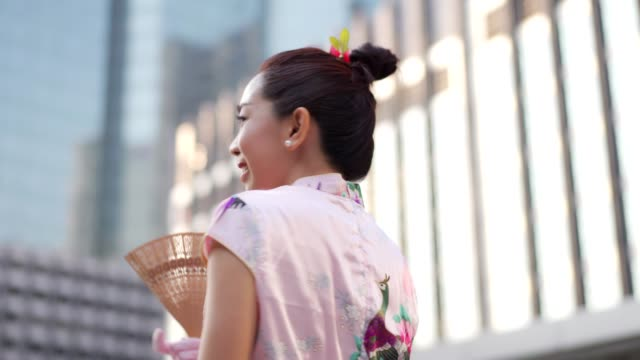 chinese woman in pink chipao smiling and holding fan. - cultura cinese video stock e b–roll