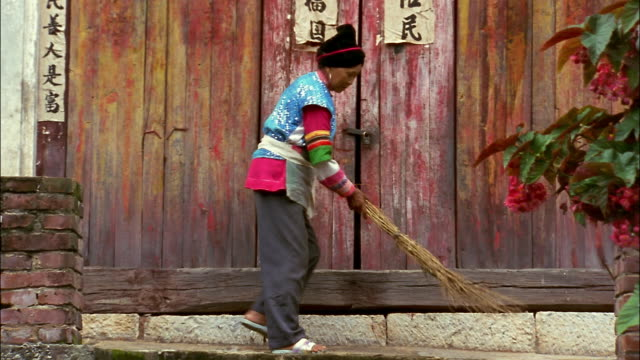 A Chinese woman in traditional clothing sweeps in front of a faded red door.