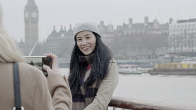 Chinese woman is being photographed by her friend, the Big Ben in background.