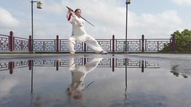 chinese woman practicing tai chi - martial arts stock videos & royalty-free footage